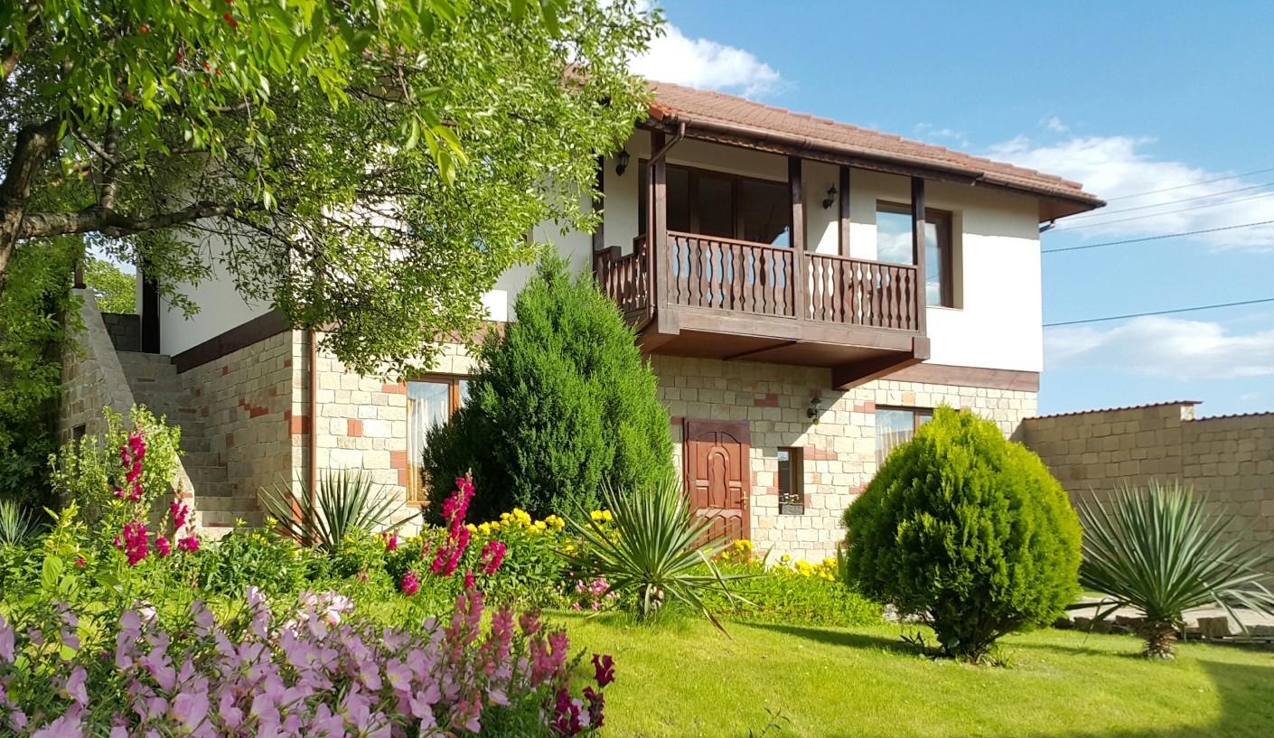 """Къща за гости """"Кьосев"""" в слънчев ден със зеленина и цветя"""
