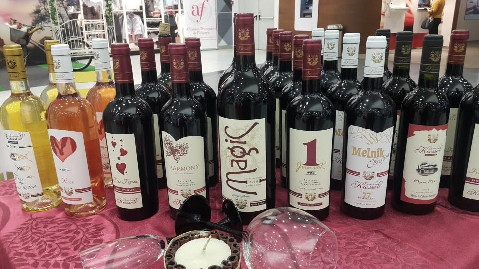 """Бутилки червено вино, бяло вино и розе """"Кьосев"""", наредени на маса по време на изложение"""